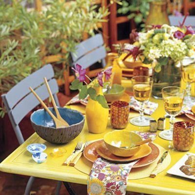 "King created this casual yet cohesive tablescape using a French raku vase, soup bowls, and salad plates, Soulé Studio chargers, Murano tumblers, Deborah Rhodes place mats, and a John Derian decoupage plate, all available at Sue Fisher King: 888-811-7276; <a href=""http://www.suefisherking.com/"" target=""_new"">suefisherking.com</a>."