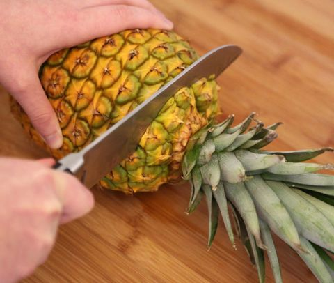 <p>Lay the pineapple on its side and cut the top.</p>