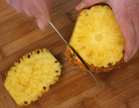 <p>Run the knife down the length of the pineapple. You want to cut in deep enough so that all the prickly brown bits are cut off. I make about seven cuts, but you could do more or less, depending on how much you chop off, and how big your pineapple is.</p>
