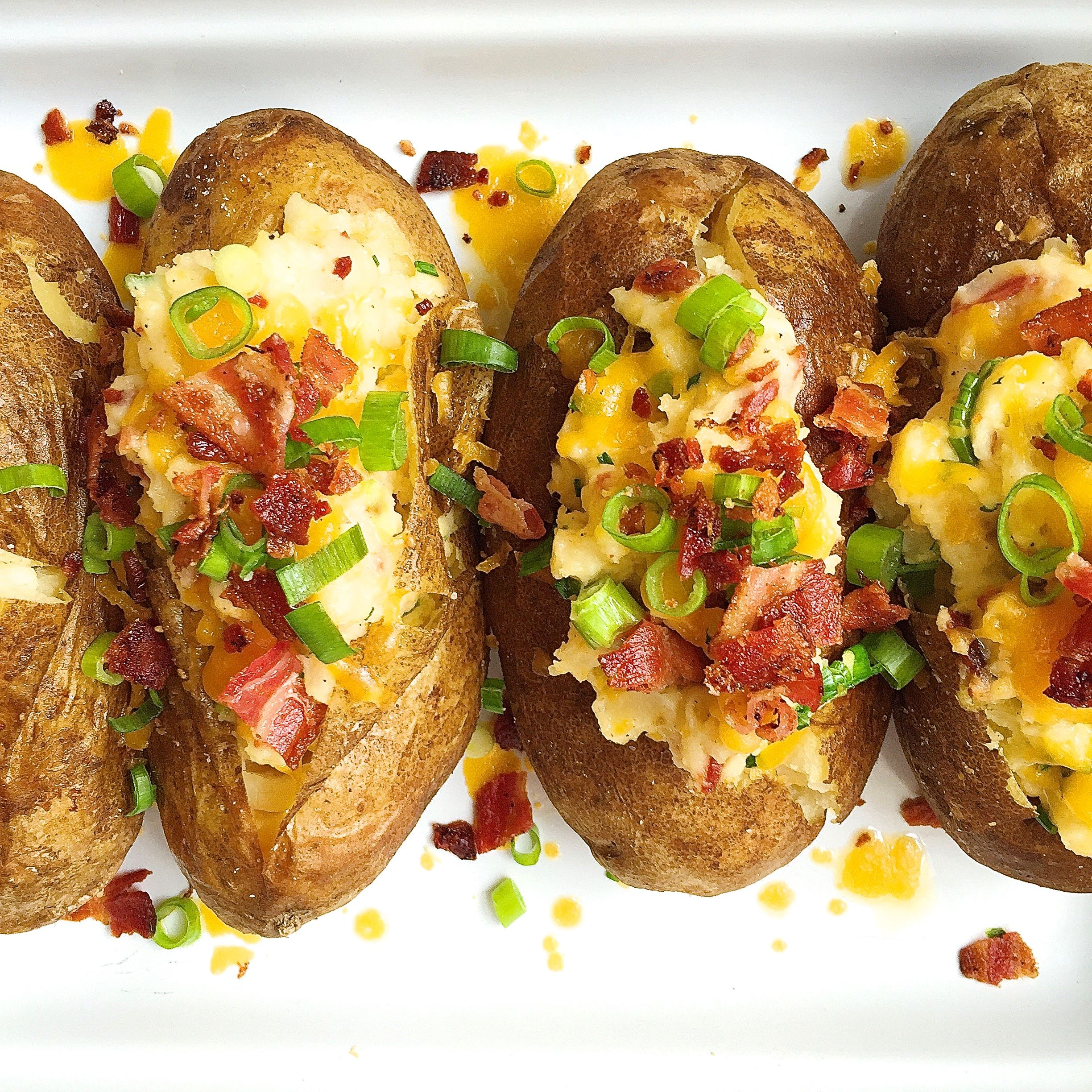 Best Loaded Baked Potatoes With Bacon And Cheddar Recipe How To Make Loaded Baked Potatoes With Bacon And Cheddar Delish Com
