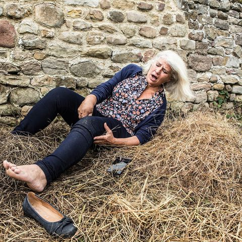 People in nature, Denim, Hay, Stone wall, Sitting, Straw, Knee, Brick, Street fashion, Thigh,