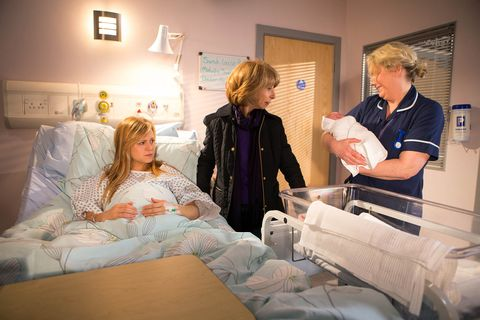 The midwife hands Sarah her baby