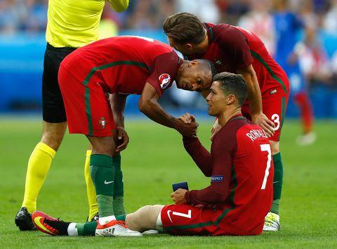 Cristiano Ronaldo of Portugal passes his captain's armband to his team mate Nani