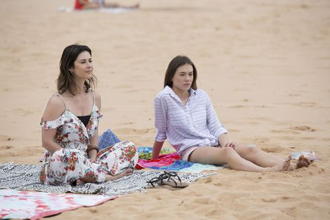 Maggie and Coco Astoni sit on the beach together in Home and Away