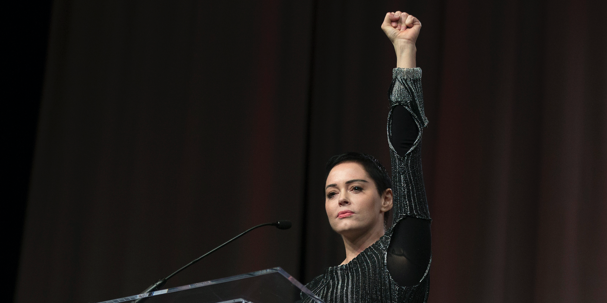 Rose McGowan raises her fist during her opening remarks to the audience at the Women's March / Women's Convention in Detroit, Michigan