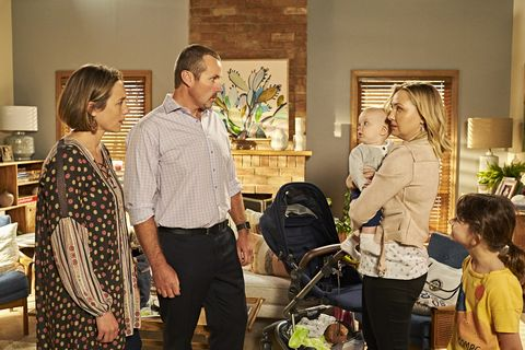 Sindi Watts hands a baby over to Toadie and Sonya Rebecchi in Neighbours
