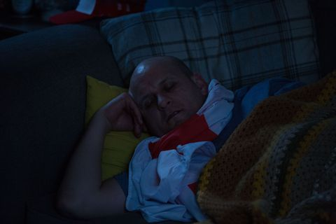 Stuart Highway is asleep on the Carters' sofa in EastEnders