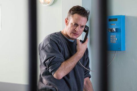 Luke Morgan takes a phone call in prison in Hollyoaks