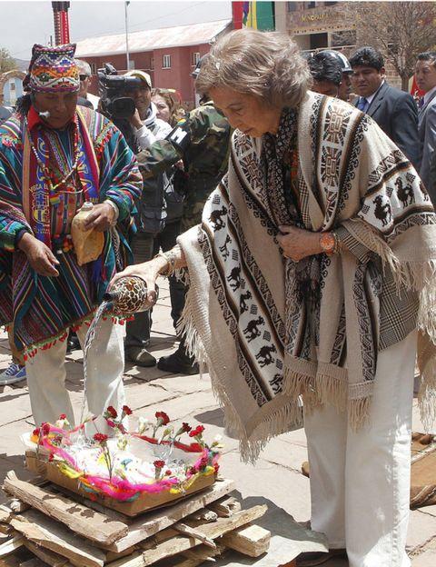 Hat, Public space, Tradition, Headgear, Temple, Street fashion, Dessert, Baked goods, Cake, Costume,