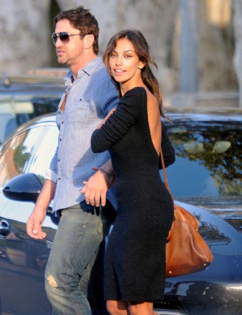 Shirt, Dress, Sunglasses, Automotive exterior, Vehicle door, Street fashion, Hood, One-piece garment, Windshield, Brown hair,