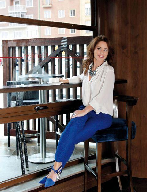 Human leg, Sitting, Denim, Knee, Electric blue, Street fashion, Hardwood, Foot, Outdoor furniture, Kitchen & dining room table,