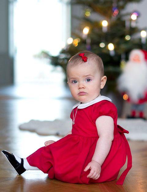Ear, Human body, Floor, Flooring, Red, Child, Dress, Baby & toddler clothing, Sitting, Toddler,