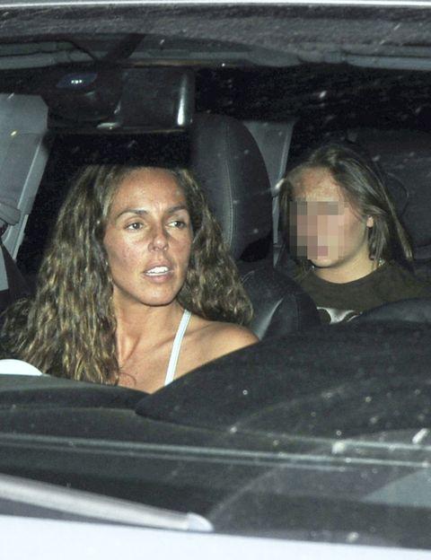 Nose, Eyebrow, Black hair, Vehicle door, Automotive window part, Car seat, Luxury vehicle, Windshield, Head restraint, Car seat cover,