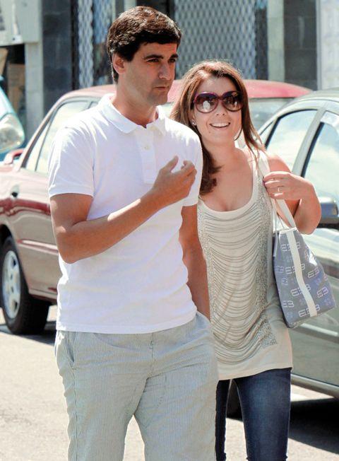 Eyewear, Vision care, Trousers, Vehicle door, Shirt, Standing, T-shirt, Sunglasses, Street fashion, Waist,