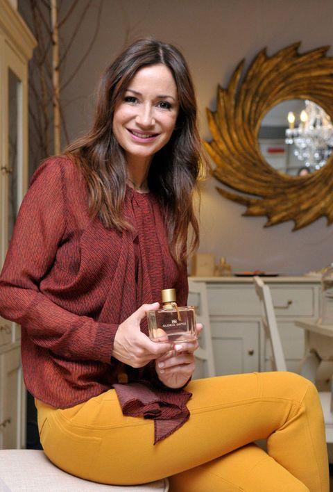 Yellow, Wine glass, Drink, Sitting, Drinkware, Stemware, Layered hair, Long hair, Barware, Sweater,