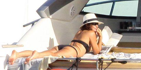 Hat, Human leg, Sitting, Swimwear, Summer, Elbow, Thigh, Brassiere, Vacation, Sun tanning,