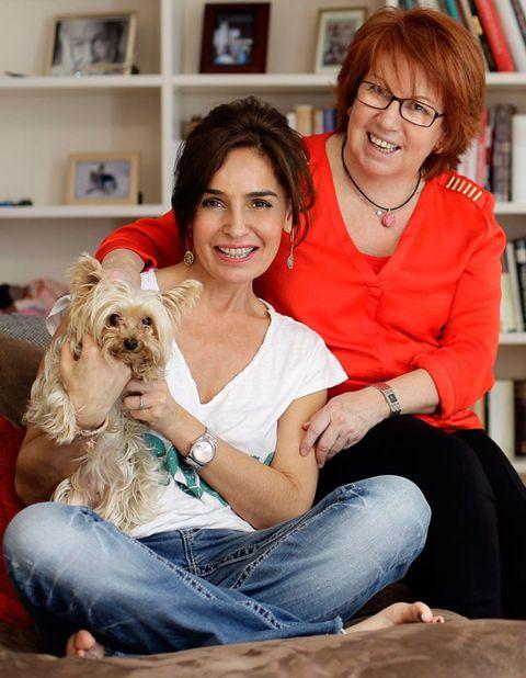 Human, Smile, Shelf, Dog breed, Vertebrate, Sitting, Bookcase, Dog, Shelving, Carnivore,