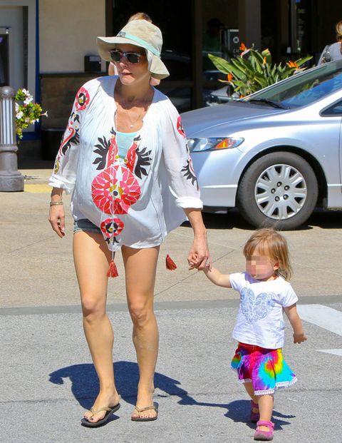Clothing, Hat, Human leg, Pink, Sunglasses, Alloy wheel, Sun hat, Full-size car, Sedan, Mid-size car,