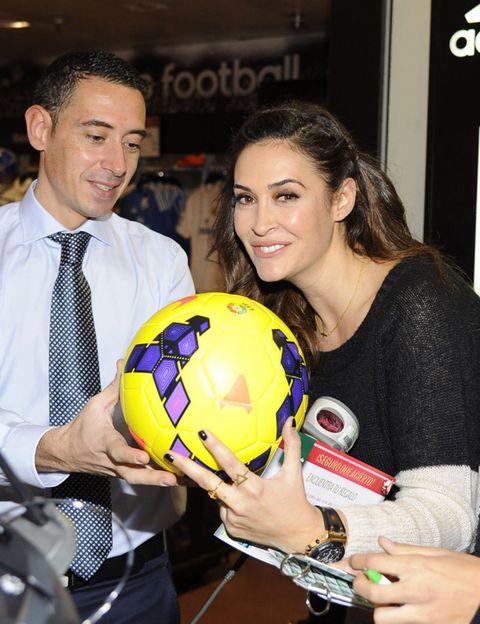 Ball, Smile, Dress shirt, Soccer ball, Football, Hand, Ball, Tie, Collar, Sweater,