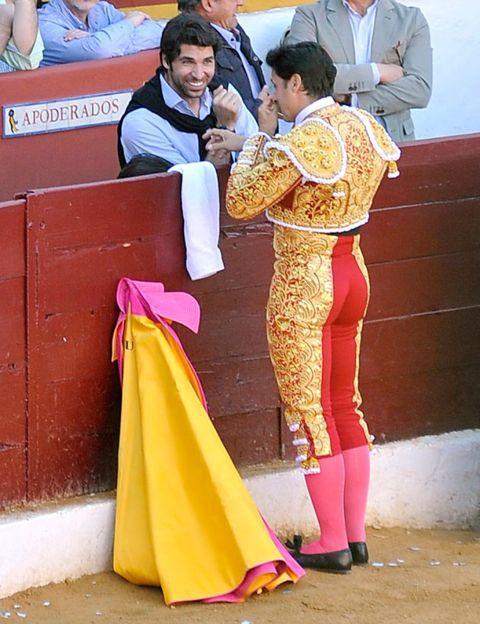 Matador, Bullring, Interaction, Magenta, Tradition, Temple, Bullfighting, Sandal, Costume, Animal sports,