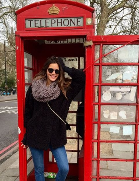 Eyewear, Vision care, Telephone booth, Red, Jeans, Denim, Standing, Photograph, Outerwear, Public space,