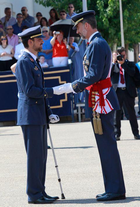 Hat, Standing, Uniform, Headgear, Suit trousers, Peaked cap, Security, Gesture, Military uniform, Law enforcement,