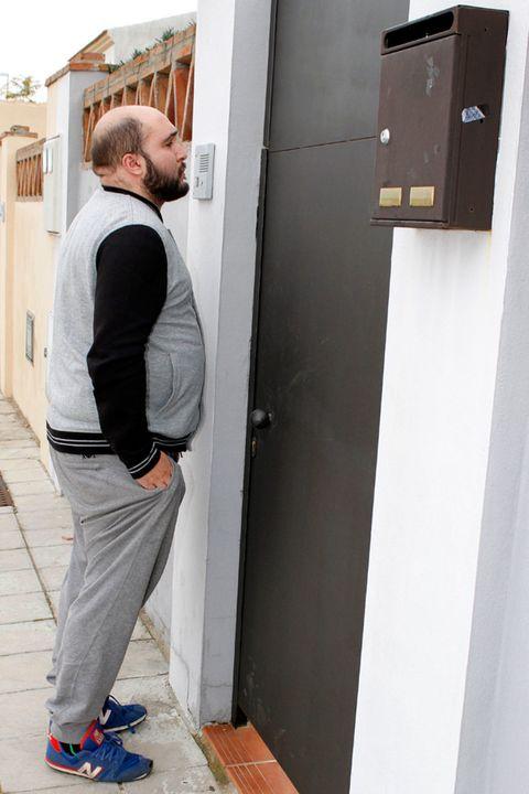 Trousers, Standing, Outerwear, Street fashion, Beard, Sneakers, Bag, Door, Outdoor shoe, Walking shoe,