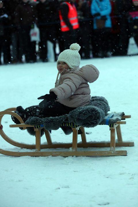 Human, Winter, Sitting, Holiday, Snow, Street fashion, Sled, Precipitation, Sun hat, Freezing,