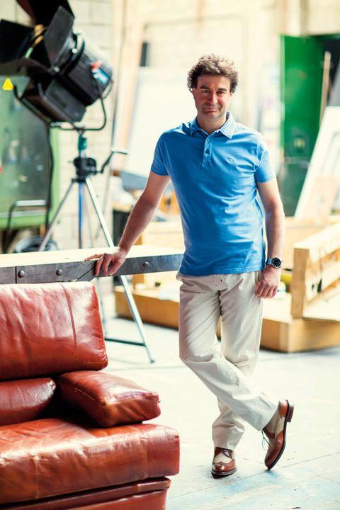 Brown, Shirt, T-shirt, Couch, Camera, Film camera, Camera accessory, Street fashion, Knee, Comfort,