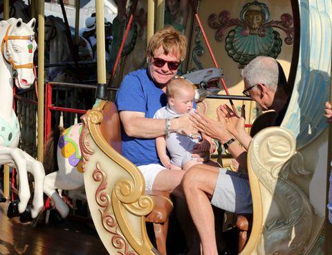 Sitting, Horse, Comfort, Carousel, Sunglasses, Amusement park, Amusement ride, Horse tack, Lap, Working animal,