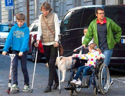 Footwear, Wheel, Human, Product, Leash, Vehicle door, Carnivore, Wheelchair, Dog, Dog walking,
