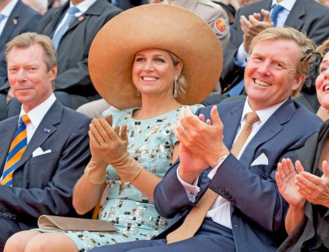 Smile, Finger, Hat, Hand, Happy, Facial expression, Sun hat, Fashion accessory, Sitting, Tie,