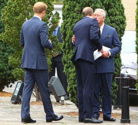 Coat, Trousers, Suit trousers, Standing, Outerwear, Suit, Formal wear, Interaction, Blazer, Pocket,