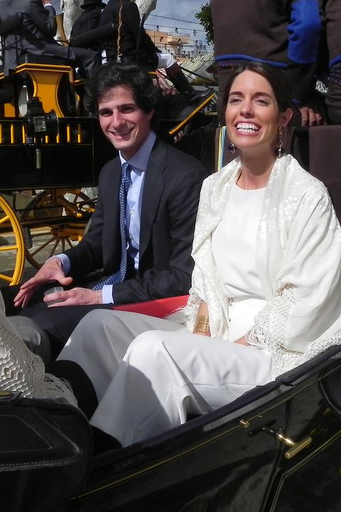 Smile, Sitting, Happy, Facial expression, Suit, Carriage, Tie, Laugh, Tradition, Classic,