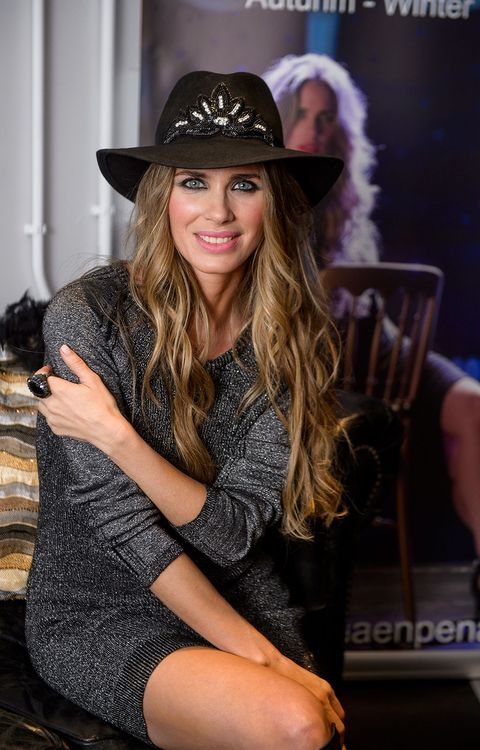 Hat, Fashion accessory, Facial expression, Style, Sitting, Beauty, Headgear, Costume accessory, Fashion, Chair,