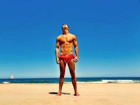 Human leg, Shoulder, Bodybuilder, Standing, Coastal and oceanic landforms, Chest, Sand, Summer, Waist, People on beach,