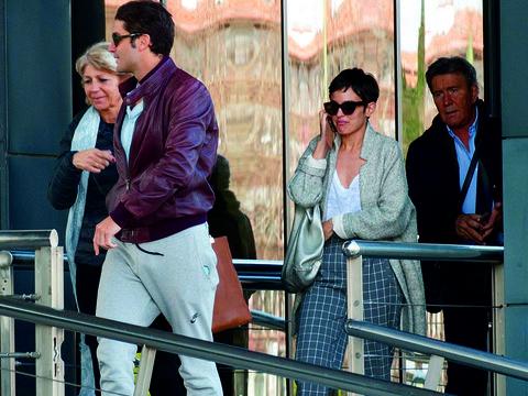 Eyewear, Trousers, Outerwear, Coat, Interaction, Jacket, Street fashion, Sunglasses, Conversation, Blazer,