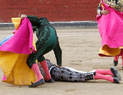Footwear, Magenta, Human leg, Purple, Pink, Tradition, Matador, Costume, Bullring, Costume design,
