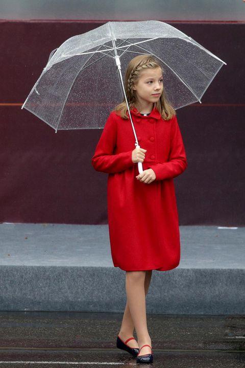 Umbrella, Red, Clothing, Outerwear, Standing, Fashion accessory, Rain, Headgear, Smile,
