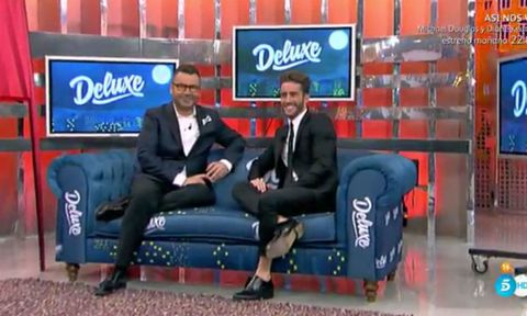 Clothing, Leg, Blue, Display device, Couch, Formal wear, Suit, Logo, Sitting, Electric blue,