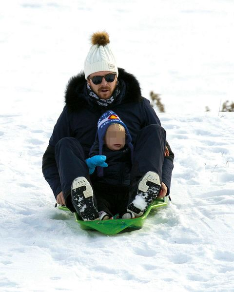 Winter, Outerwear, Playing in the snow, Mammal, Goggles, Jacket, Snow, Sitting, Sledding, Winter sport,