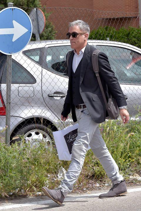 Suit, Footwear, Vehicle, Vehicle door, Street fashion, Outerwear, Car, Blazer, Shoe, Walking,