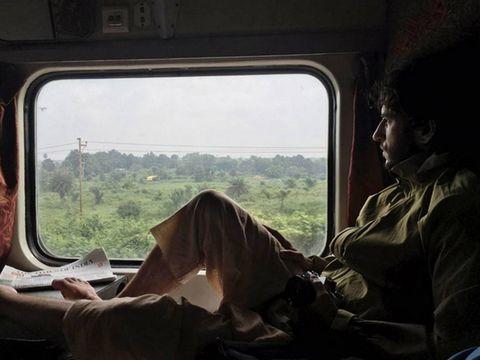 Transport, Sitting, Comfort, Boot, Public transport, Train, Reading, Passenger, Military person, Rolling stock,