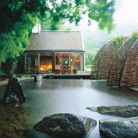 "In <a target=""_blank"" href=""http://www.elledecor.com/design-decorate/house-interiors/g733/zen-mastery-sweden-home/"">Johan Dieden's Swedish house</a>, designed by architects Gert and Karin Wingårdh, woven-willow arches lead to the glass-wall structure, set above a reflecting pool."