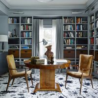 In the husband's study, the Vladimir Kagan armchairs and pendant fixture by Chris Lehrecke are from Ralph Pucci, the 1930s walnut table is Italian, and the custom carpet is by Kelly Wearstler.