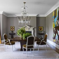 Adam-style dining chairs covered in a Lee Jofa mohair surround a custom-made table, the George II–style fireplace surround is from Jamb, and the painting is by Mickalene Thomas&#x3B; the walls are painted in Benjamin Moore's Baja Dunes.