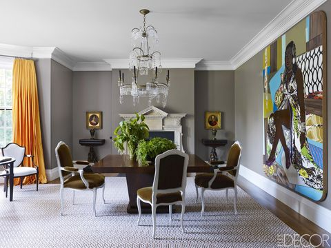 Adam-style dining chairs covered in a Lee Jofa mohair surround a custom-made table, the George II–style fireplace surround is from Jamb, and the painting is by Mickalene Thomas; the walls are painted in Benjamin Moore's Baja Dunes.