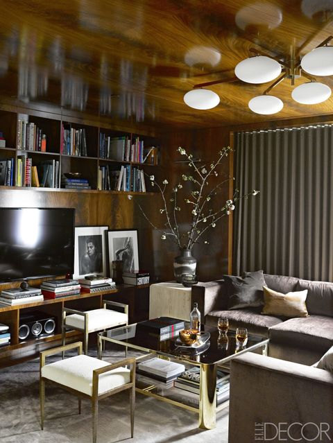 A custom sectional sofa, a cocktail table by Madeline Stuart, and stools by Magni Home Collection in the den; the vintage ceiling fixture is by Angelo Lelli for Arredoluce, and the custom cabinetry is sheathed in a mahogany veneer.
