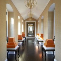 Chairs by Schumacher line an upstairs corridor&#x3B; the light fixtures are custom made, and the wallcovering is by Élitis.