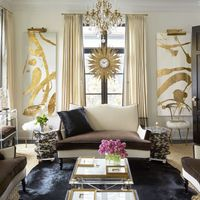 In the living room of the Lake Forest, Illinois, home that designer Megan Winters shares with her husband, Patrick, the Lucite console, gilt chairs flanking the window, and settees, which are covered in Schumacher fabrics, are all by Megan Winters Collection&#x3B; the artworks are by Allison Cosmos, and the French sunburst clock is a Paris flea-market find.